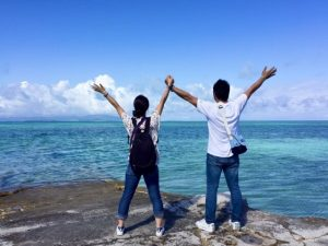 海に向かって手を挙げる男女