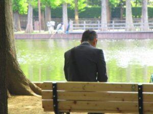池のベンチで休憩するサラリーマン